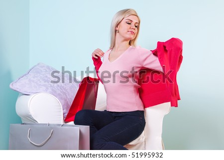 An attractive blond woman sat in a chair trying on some new clothes she's just bought.