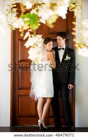 An attractive bride and groom getting married outdoors - stock photo