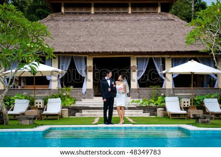 An attractive bride and groom smiling at each other at a villa outdoors - stock photo