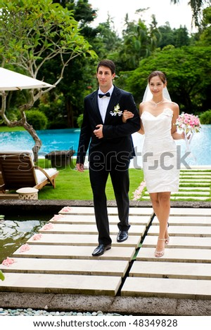 An attractive bride and groom walking down a pathway outdoors - stock photo