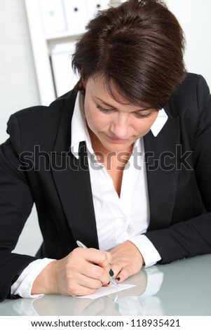 An attractive brunette businesswoman sitting at her desk, concentrates on making some notes - stock photo