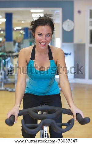 An attractive brunette working out on an exercise bike at the gym - stock photo