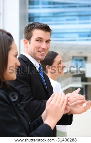 An attractive business man and woman team clapping at office building - stock photo