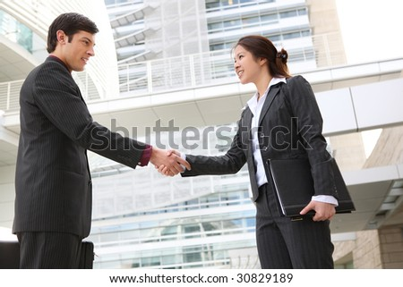 An attractive business man and woman team shaking hands - stock photo