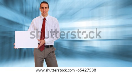 An attractive business man holding a white add in a light business environment - stock photo