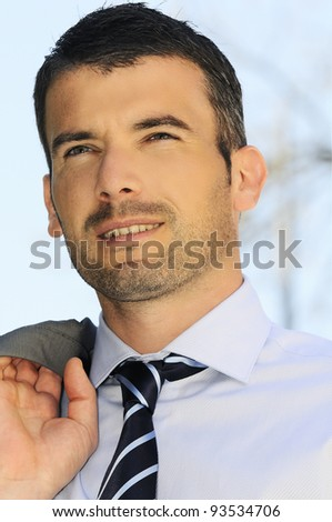 An attractive business man is walking outdoor - stock photo