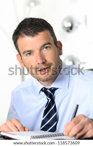 An attractive business man is writing on a paper - stock photo