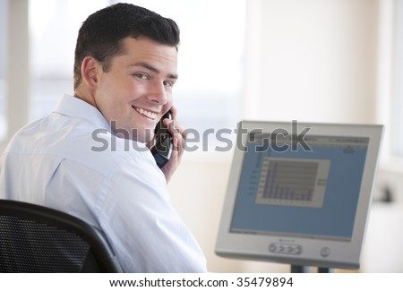 An attractive business man working on a computer and talking on a cellphone.  He has a bar chart on his computer screen and is smiling at the camera.  Horizontally framed shot.