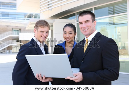 An attractive business team at the office with laptop computer