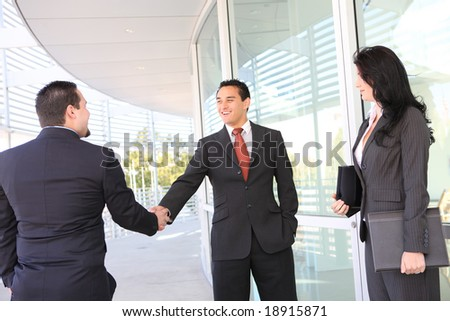 An attractive business team handshake at office building - stock photo
