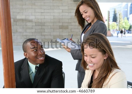 An attractive business team interacting at their workplace - stock photo