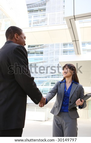 An attractive business team shaking hands at office building