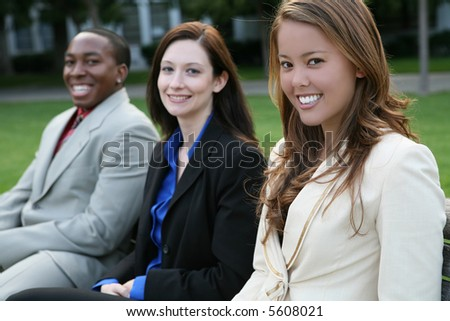 An attractive business team sitting on a bench - stock photo