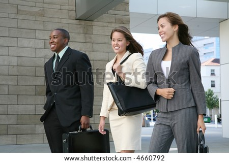 An attractive business team walking composed of two women and a man - stock photo