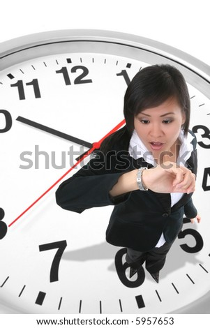 An attractive business woman standing on a clock and looking at her watch - stock photo