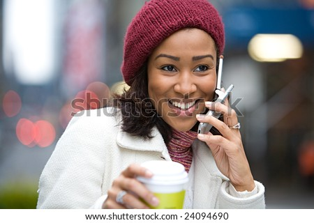 An attractive business woman talking on her cell phone along with a hot coffee. - stock photo