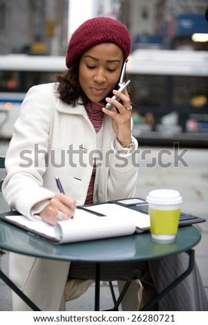 An attractive business woman talking on her cell phone and writing something down in her notes. - stock photo