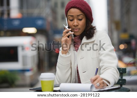 An attractive business woman talking on her cell phone and writing something down in her notes.