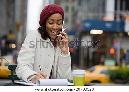 An attractive business woman talking on her cell phone while seated outdoors in the city. - stock photo