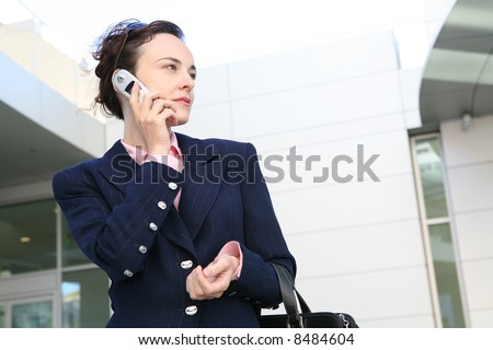 An attractive business woman talking on the phone outside her office - stock photo