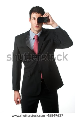 An attractive businessman holding a mobile phone to his eye against white background