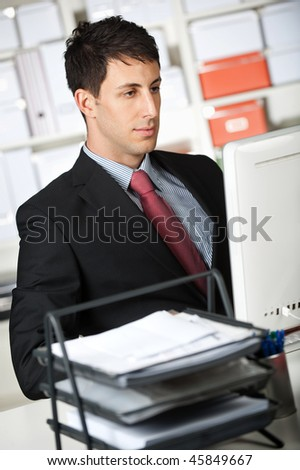 An attractive businessman using his computer at the office