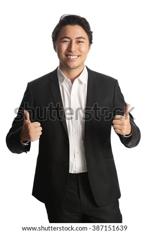 An attractive businessman wearing a black suit with a white shirt, standing against a white background doing thumbs up with both hands.