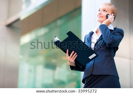 An attractive businesswoman holding a clipboard and talking on the phone in the city
