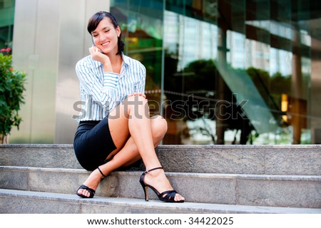 An attractive businesswoman sitting down on some steps outside her office in the city having a conversation - stock photo