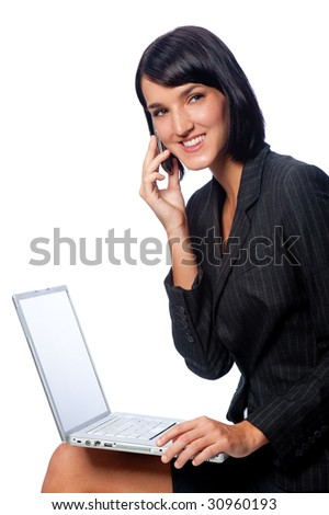 An attractive businesswoman sitting down with a laptop and using a phone on white background
