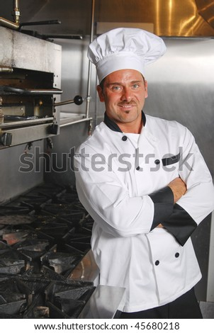 An attractive Caucasian chef leans casually against a stove in a commercial kitchen