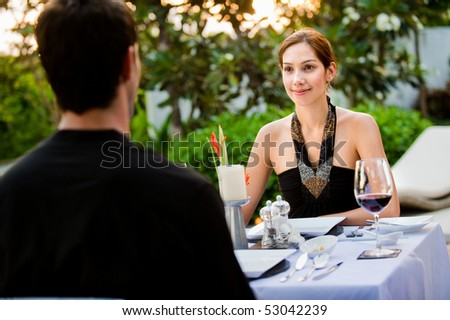 An attractive caucasian couple having a formal meal outdoors - stock photo