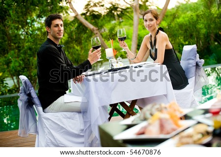 An attractive caucasian couple having a formal meal with red wine outdoors - stock photo