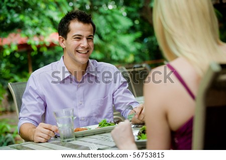 An attractive caucasian couple having a meal at an outdoor restaurant - stock photo