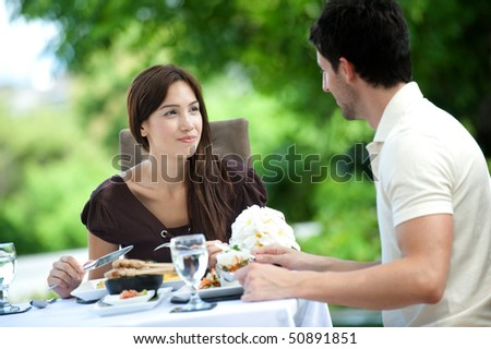 An attractive caucasian couple having a relaxing meal outdoors together - stock photo