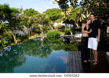 An attractive caucasian couple relaxing and lounging outdoors by a pool - stock photo
