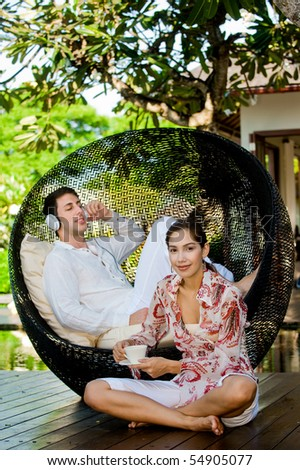 An attractive caucasian couple relaxing with a laptop outdoors - stock photo