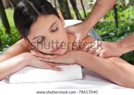 An attractive Caucasian woman getting massaged by a therapist - stock photo