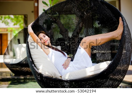 An attractive caucasian woman relaxing and lounging outdoors - stock photo