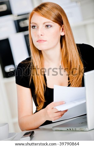 An attractive caucasian woman thinking with pen and paper in hand at the office, with a laptop, phone and a drink on the table