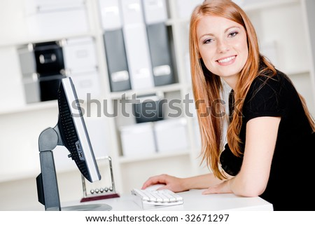 An attractive caucasian woman using the computer in an office