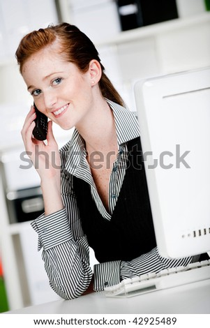 An attractive caucasian woman using the phone in the office