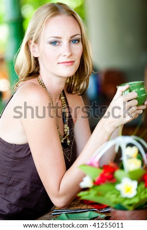 An attractive caucasian woman with a drink in a restaurant - stock photo