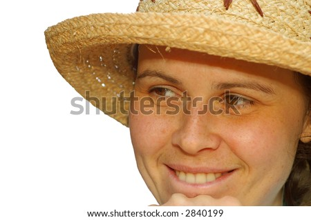 An attractive coquettish young girl in a straw hat smiles mischievously biting lower lip isolated on white. - stock photo
