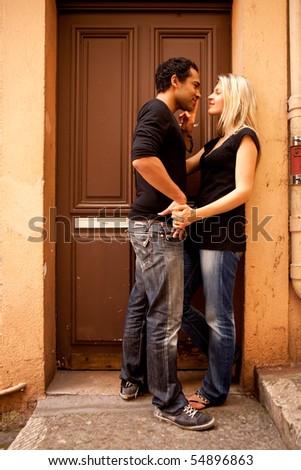 An attractive couple flirting in an outdoor European setting - stock photo