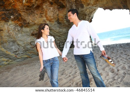 An attractive couple having fun at the beach - stock photo