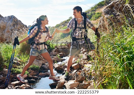An attractive couple holding hands as the man helps his girlfriend across the stream of their hiking trail - stock photo
