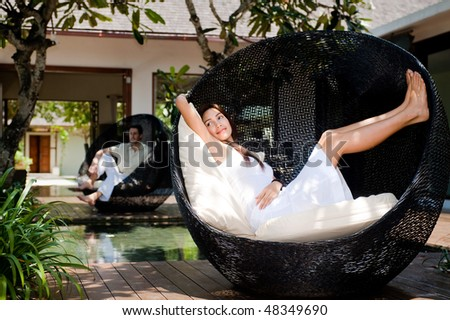 An attractive couple lounging and relaxing on chairs outdoors - stock photo