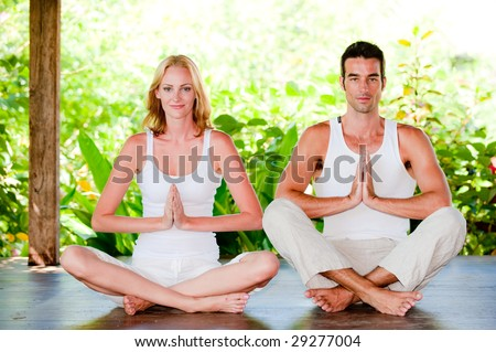 An attractive couple practicing yoga outdoors - stock photo