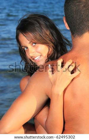 An attractive couple relaxing at the beach, at sunset - stock photo